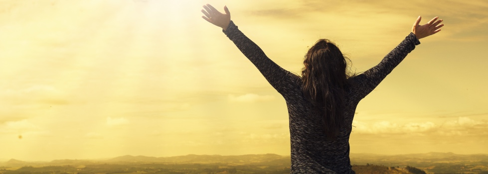 A woman stands facing the horizon and golden sky with her arms raised wide above her head